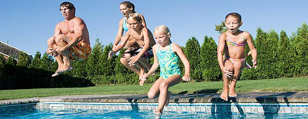Family jumping into swimming pool