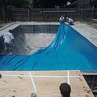 Workers installing in-ground pool liner